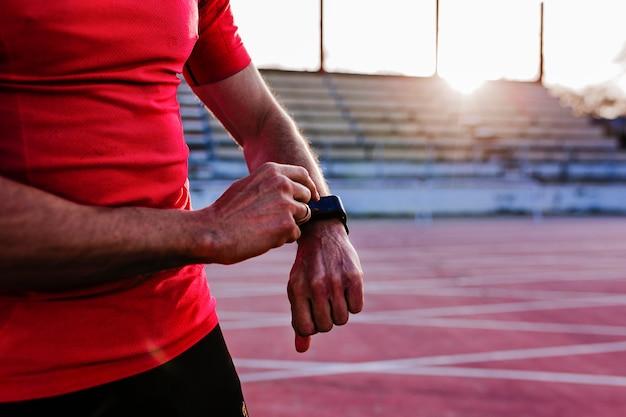 Uomo giovane corridore controllando l'orologio nella corsia di atletica leggera. fai sport all'aperto