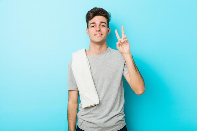 Uomo giovane dell'adolescente di forma fisica che mostra numero due con le dita.