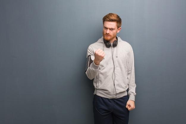 Uomo giovane di redhead di forma fisica che mostra pugno alla fronte, espressione arrabbiata
