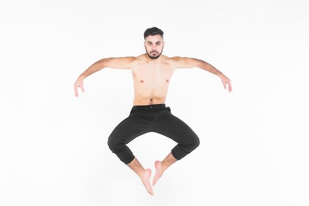 Uomo giovane e acrobata che fa esercizio nell'aria