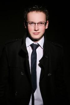 Uomo giovane e alla moda sul nero