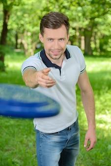 Uomo giovane e bello che gioca frisbee nel parco