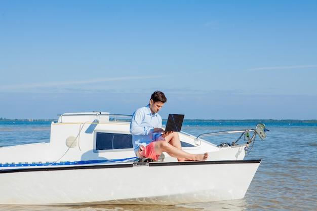 Uomo giovane e bello con il computer portatile sulla barca a vela. concetto di lavoro freelance