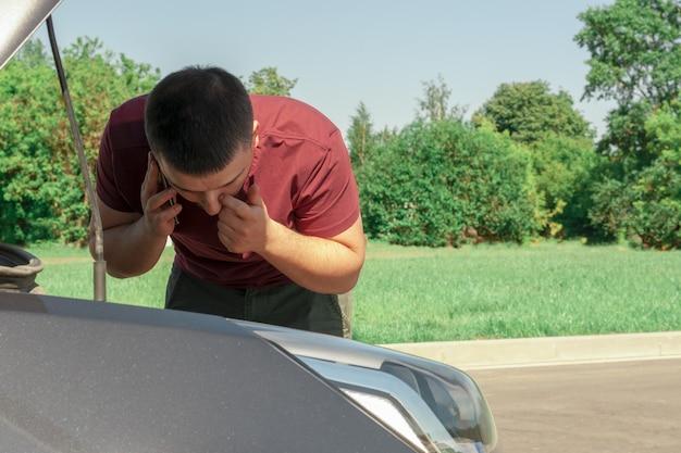 Uomo giovane e bello vicino a un'auto rotta con un cofano aperto, parlando al telefono.