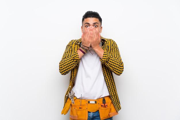 Uomo giovane elettricista sopra il muro bianco isolato con espressione facciale a sorpresa