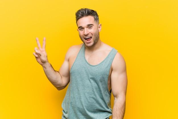 Uomo giovane fitness contro un giallo gioioso e spensierato mostrando un simbolo di pace con le dita.