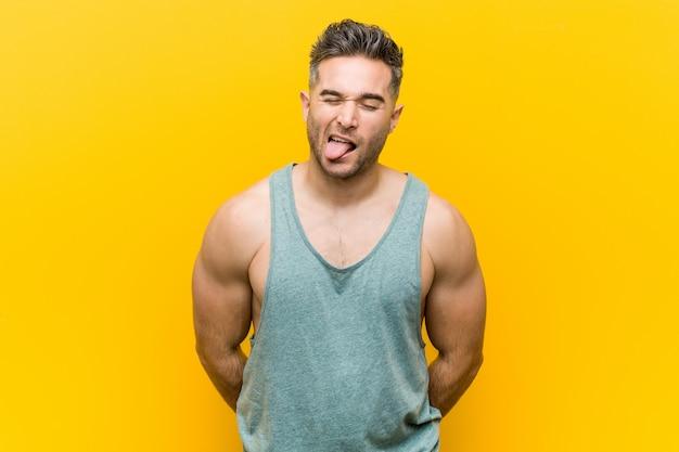 Uomo giovane fitness, divertente e amichevole che attacca fuori lingua