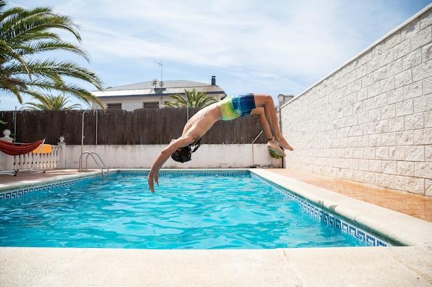 Uomo giovane fitness saltando in acqua in piscina un giorno di vacanze estive
