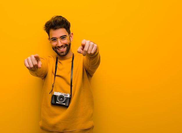 Uomo giovane fotografo allegro e sorridente