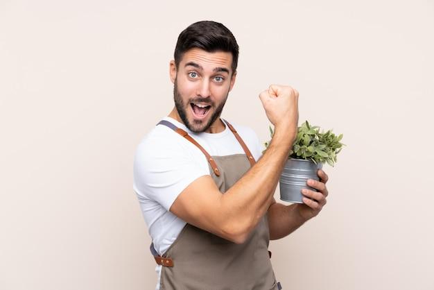 Uomo giovane giardiniere sopra la parete isolata