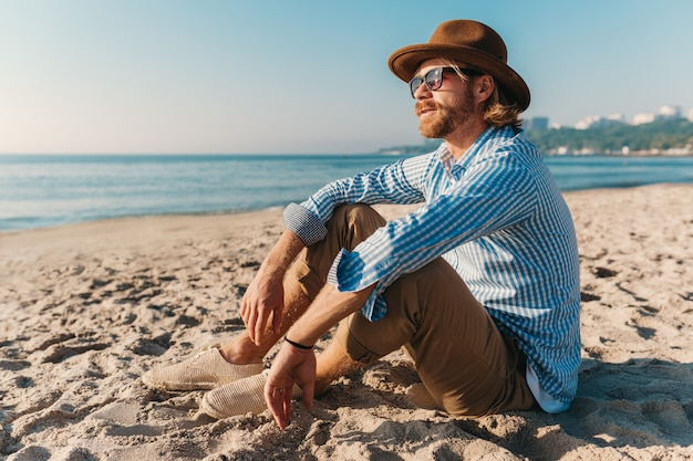 Uomo giovane hipster seduto sulla spiaggia in riva al mare in vacanza estiva, vestito in stile boho, vestito con una camicia