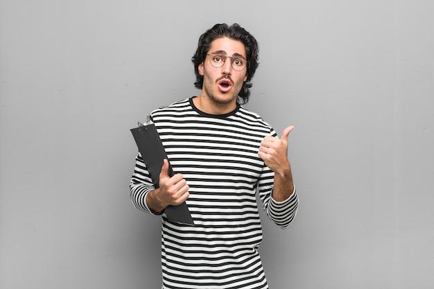 Uomo giovane impiegato in possesso di un inventario che punta verso il lato