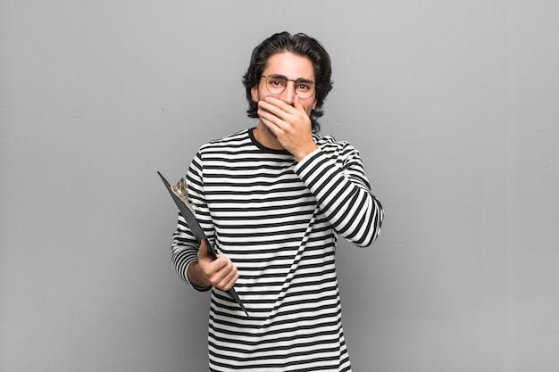 Uomo giovane impiegato in possesso di un inventario ridendo di qualcosa, coprendo la bocca con le mani.