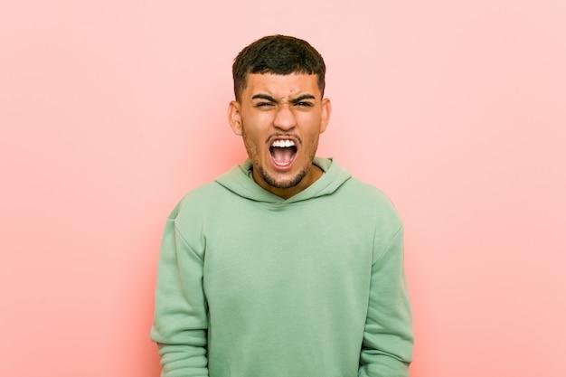 Uomo giovane ispanico di sport che grida molto arrabbiato e aggressivo.