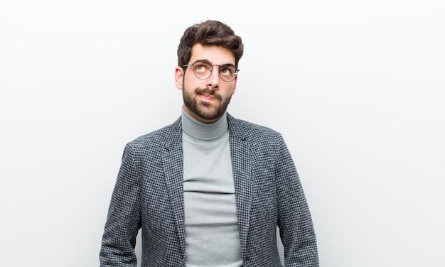 Uomo giovane manager alla ricerca perplesso e confuso, chiedendosi o cercando di risolvere un problema o pensando contro il muro bianco