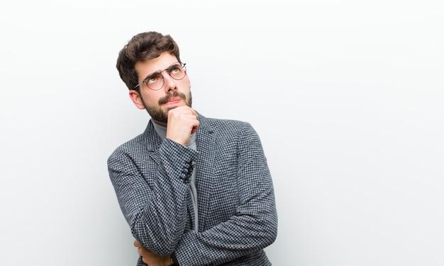 Uomo giovane manager che pensa, si sente dubbioso e confuso, con diverse opzioni, chiedendosi quale decisione prendere il muro bianco