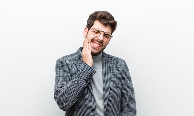 Uomo giovane manager tenendo la guancia e soffrendo di mal di denti dolorosi, sentirsi male, miserabile e infelice, in cerca di un dentista muro bianco