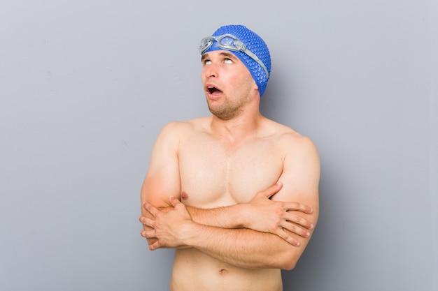 Uomo giovane nuotatore professionista stanco di un compito ripetitivo.