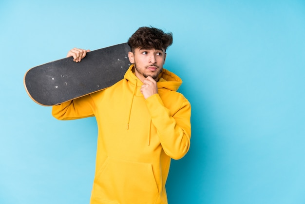Uomo giovane pattinatore arabo isolato guardando lateralmente con espressione dubbiosa e scettica.