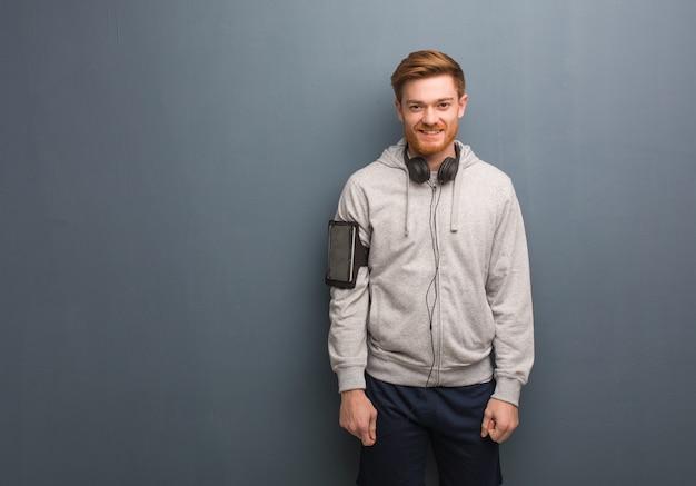Uomo giovane rossa di forma fisica allegro con un grande sorriso