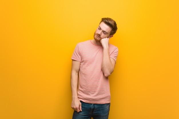 Uomo giovane rossa pensando a qualcosa, guardando al lato