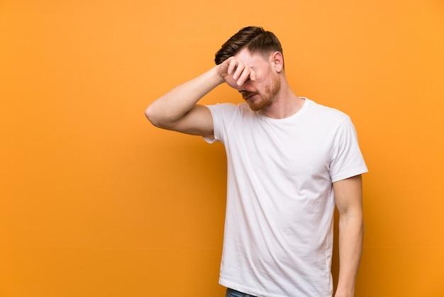 Uomo giovane rossa stressato su sfondo arancione