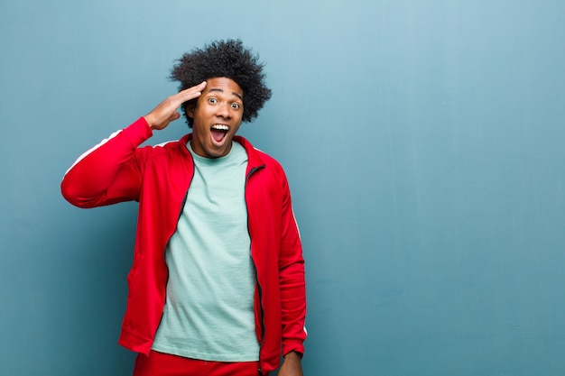 Uomo giovane sportivo che sembra felice, stupito e sorpreso, sorridente e realizzando sorprendenti e incredibili buone notizie sul muro del grunge