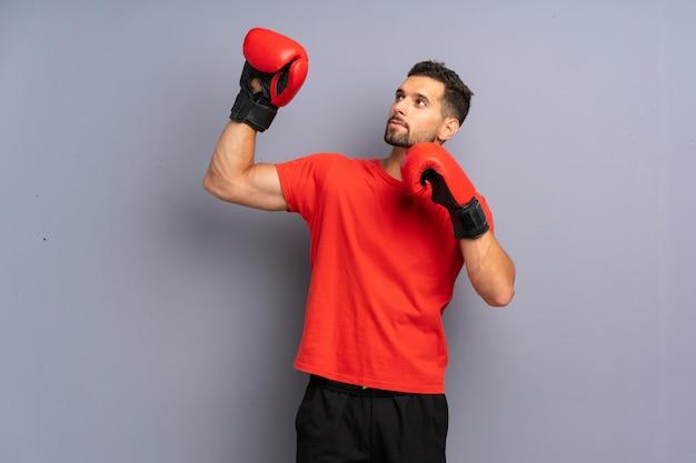 Uomo giovane sportivo con guantoni da boxe