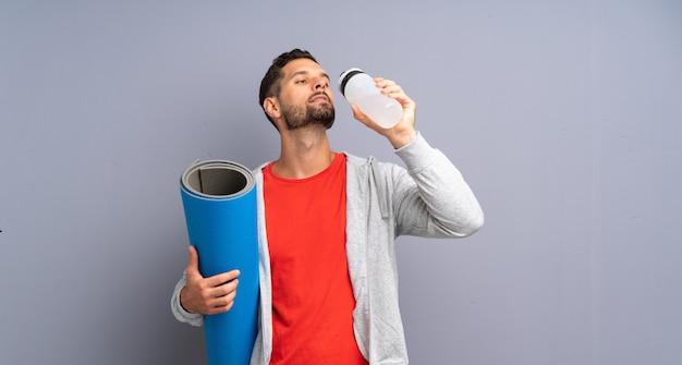 Uomo giovane sportivo con tappetino e con una bottiglia d'acqua