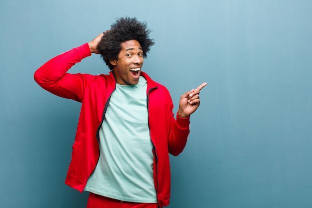 Uomo giovane sportivo nero che ride, che sembra felice, positivo e sorpreso, realizzando una grande idea che punta allo spazio laterale della copia contro la parete del grunge