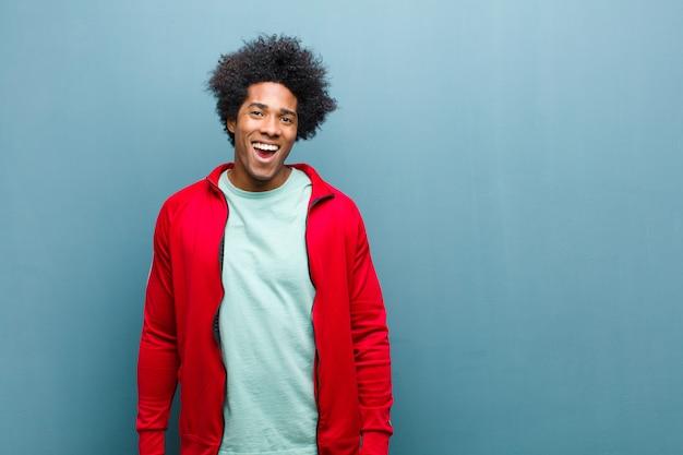 Uomo giovane sportivo nero che sembra felice e piacevolmente sorpreso, eccitato con un'espressione affascinata e scioccata