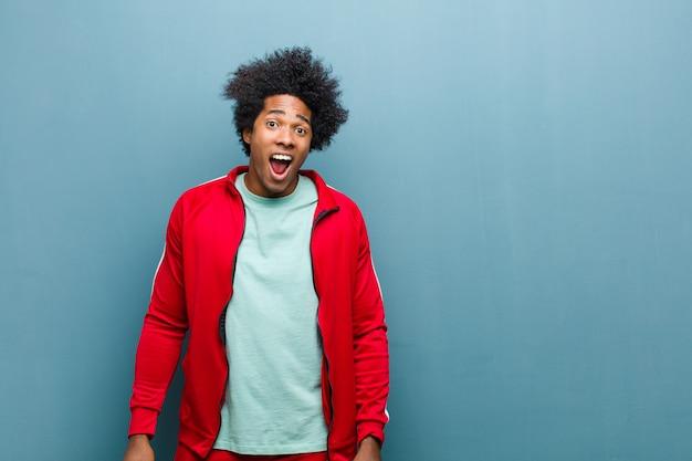 Uomo giovane sportivo nero che sembra molto scioccato o sorpreso, fissando con la bocca aperta dicendo wow contro grunge