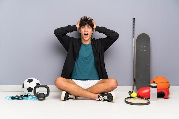 Uomo giovane sportivo seduto sul pavimento intorno a molti elementi sportivi con espressione facciale sorpresa