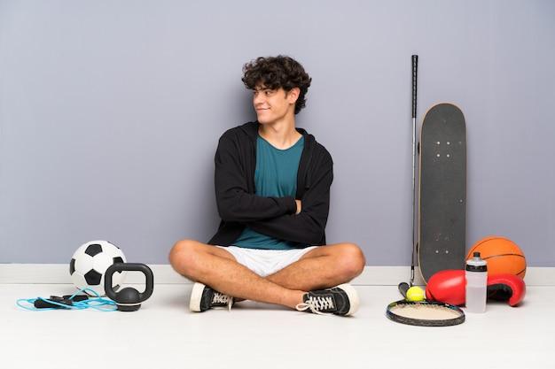Uomo giovane sportivo seduto sul pavimento intorno a molti elementi sportivi ridendo