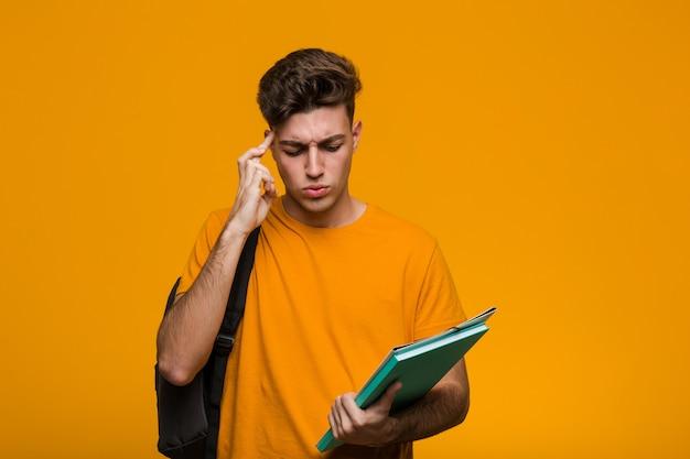 Uomo giovane studente che tiene i libri scioccati, ha ricordato un incontro importante.
