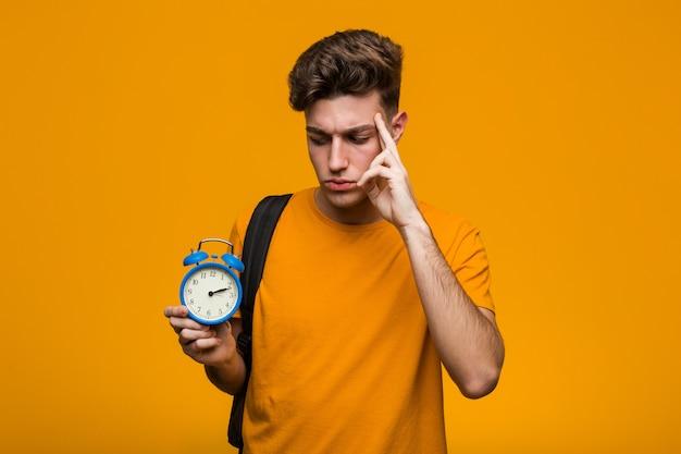 Uomo giovane studente in possesso di una sveglia cercando di ascoltare un gossip