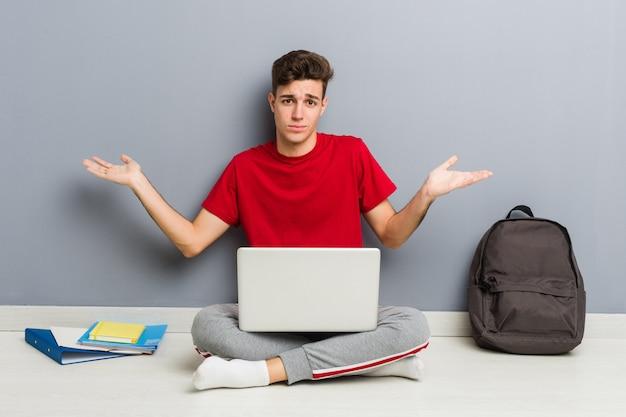 Uomo giovane studente seduto sul suo pavimento di casa in possesso di un computer portatile