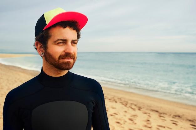 Uomo giovane surfista sulla spiaggia che indossa il cappello
