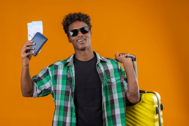 Uomo giovane viaggiatore afroamericano che indossa occhiali da sole neri in piedi con la valigia in possesso di biglietti aerei sorridendo allegramente positivo e felice su sfondo arancione