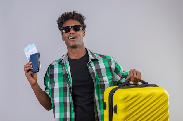Uomo giovane viaggiatore afroamericano che indossa occhiali da sole neri in piedi con la valigia in possesso di biglietti aerei sorridendo allegramente positivo e felice su sfondo bianco