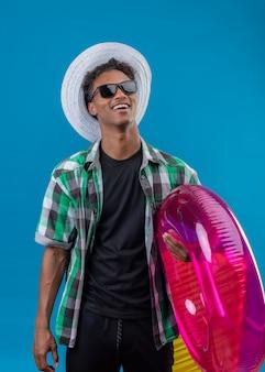 Uomo giovane viaggiatore afroamericano in cappello estivo che indossa occhiali da sole neri che tengono anello gonfiabile sorridente allegramente felice e positivo in piedi su sfondo blu
