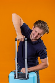 Uomo giovane viaggiatore bello che tiene la valigia alla ricerca di malessere che soffre di peso elevato in piedi su sfondo arancione