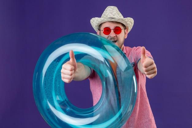 Uomo giovane viaggiatore bello in cappello estivo con anello gonfiabile che mostra i pollici in su