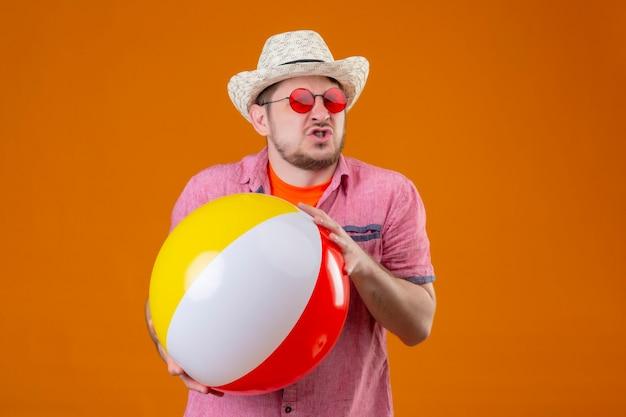 Uomo giovane viaggiatore bello in cappello estivo tenendo palla gonfiabile sensazione irritata