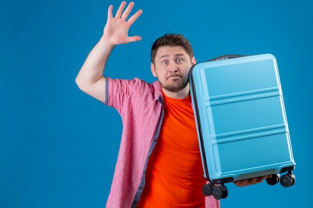 Uomo giovane viaggiatore bello spaventato che tiene la valigia alzando la mano