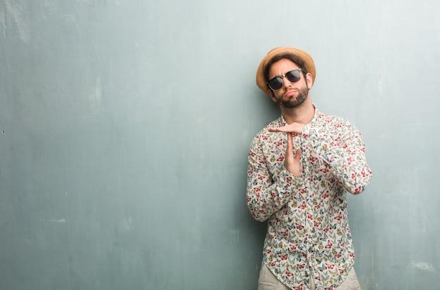 Uomo giovane viaggiatore che indossa una camicia colorata stanco e annoiato, facendo un gesto di timeout