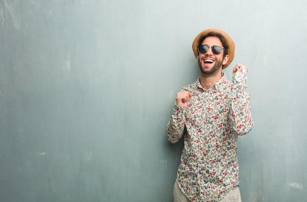 Uomo giovane viaggiatore che indossa una maglietta colorata ascoltando musica, ballando e divertendosi