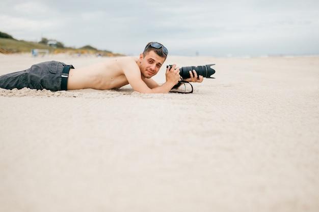 Uomo giovane viaggiatore che si trova sulla spiaggia vicino al mare in vacanza e fare foto della natura.