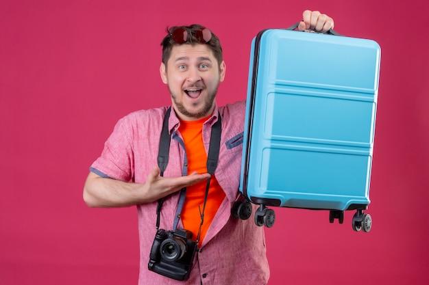 Uomo giovane viaggiatore con la valigia della holding della macchina fotografica che guarda l'obbiettivo felice ed è uscito sorridendo allegramente in piedi su sfondo rosa