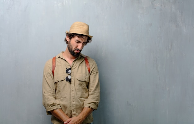 Uomo giovane viaggiatore con uno sguardo triste di delusione e sconfitta